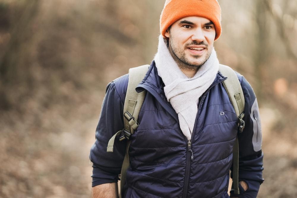 man in black zip up jacket wearing orange knit cap