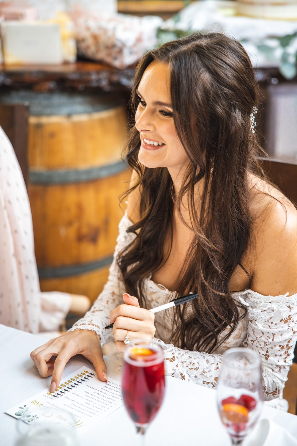 woman in white lace dress holding clear drinking glass
