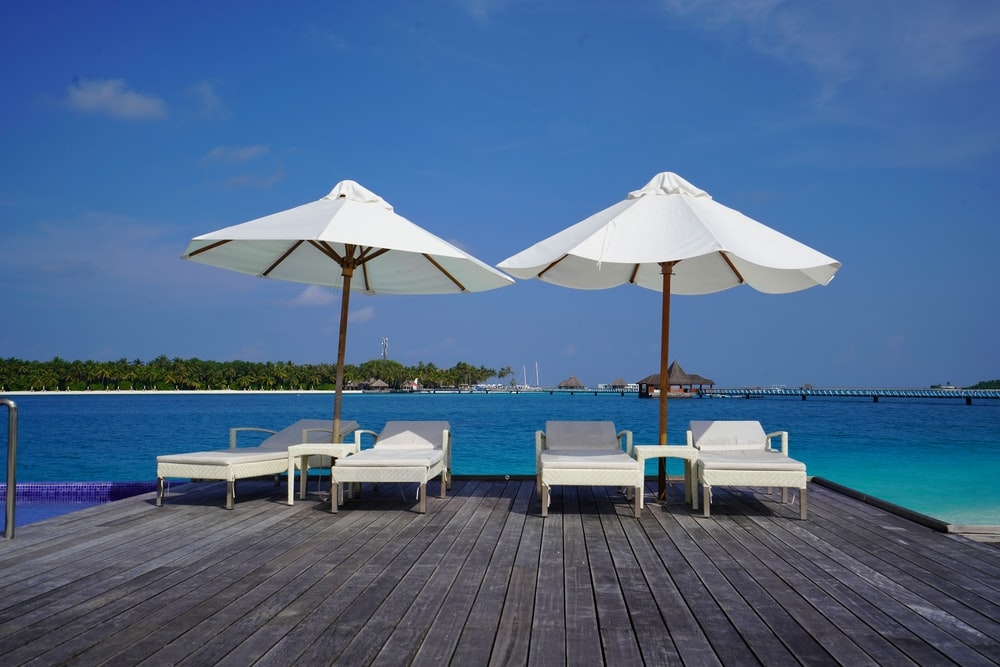 white and brown patio umbrella on brown wooden dock during daytime