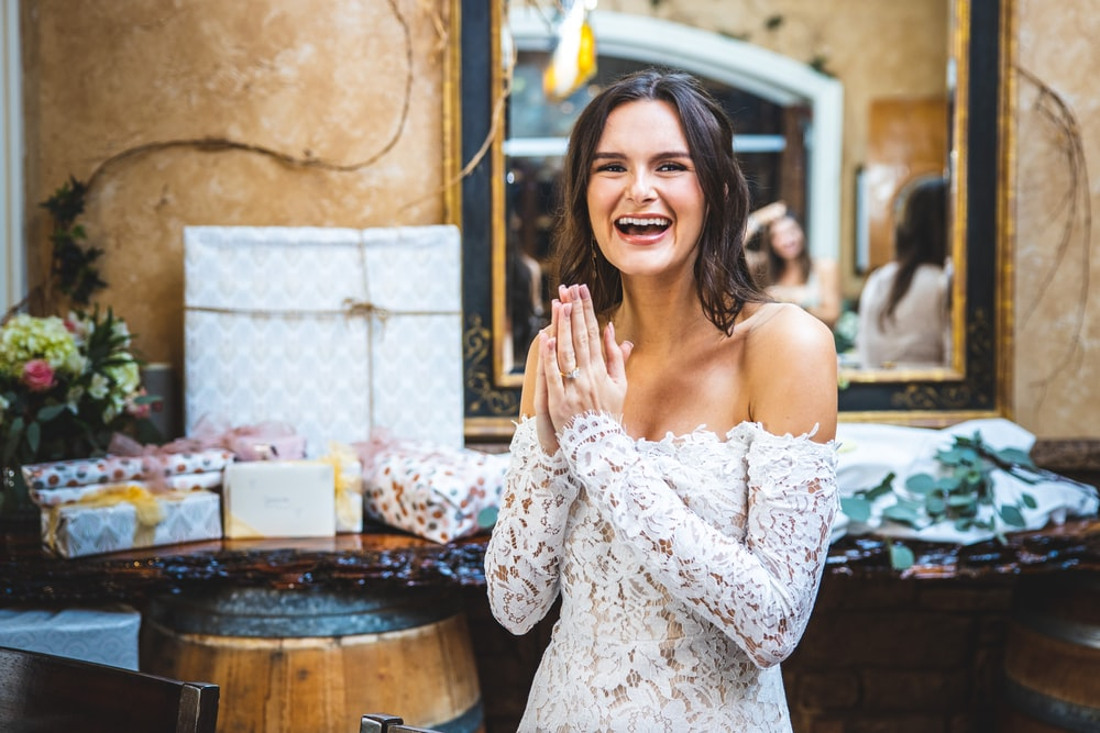 woman in white floral off shoulder dress smiling
