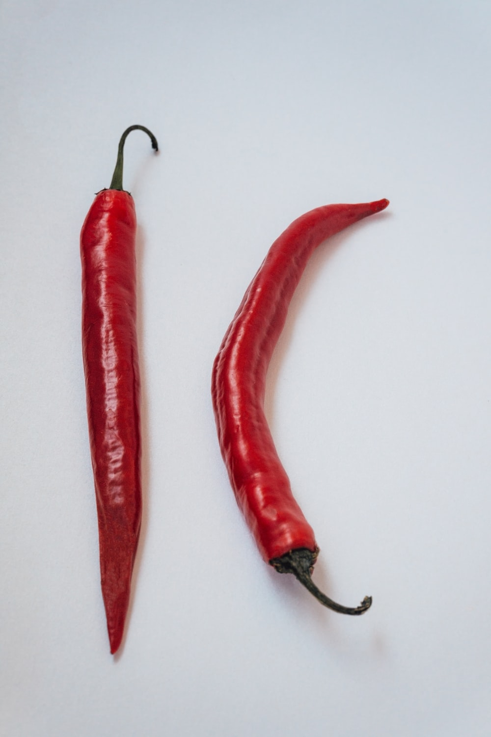 3 red chili on white surface