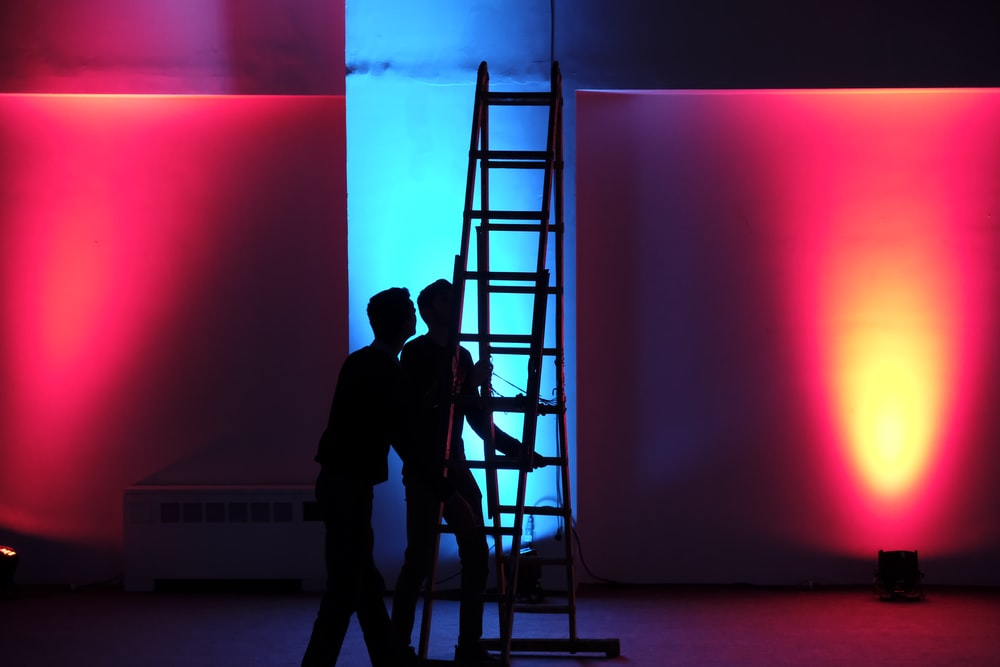 man in black jacket standing on black ladder