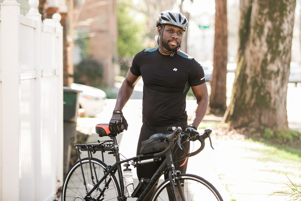 man in black crew neck t-shirt and white helmet riding on black bicycle during daytime