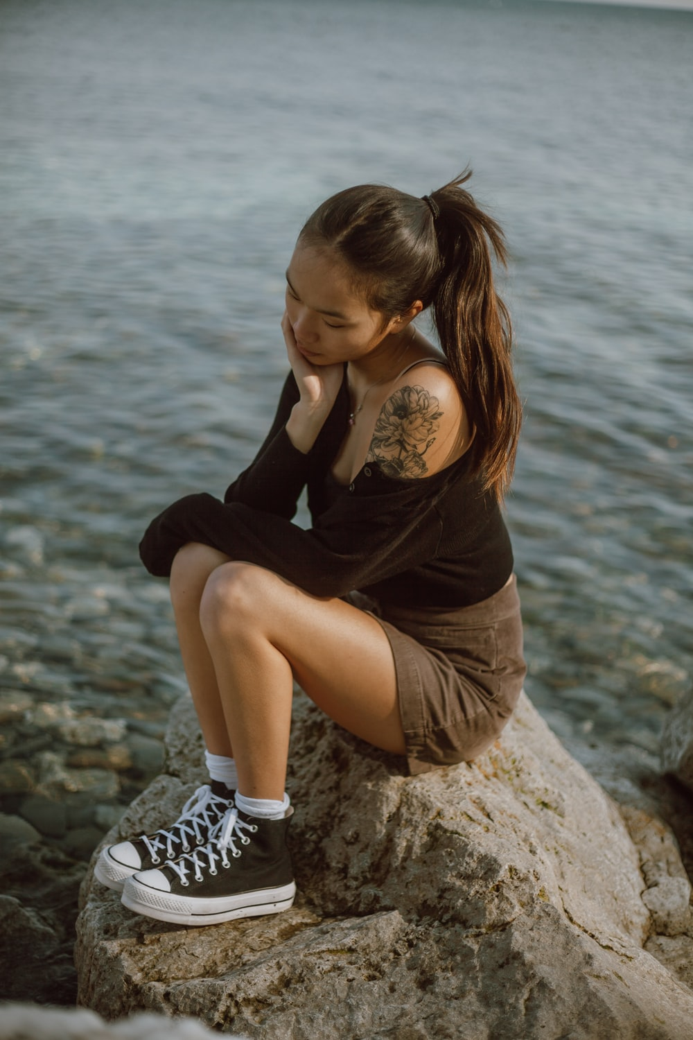 woman in black long sleeve shirt and black and white shorts sitting on rock near body