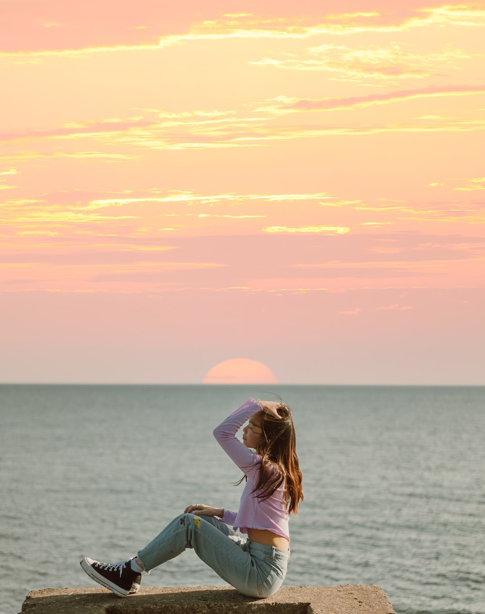 woman in white shirt and blue denim jeans sitting on blue and white boat during sunset