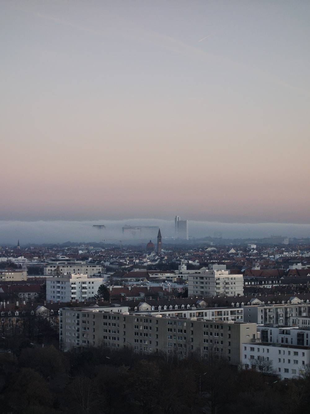 city with high rise buildings under white sky during daytime
