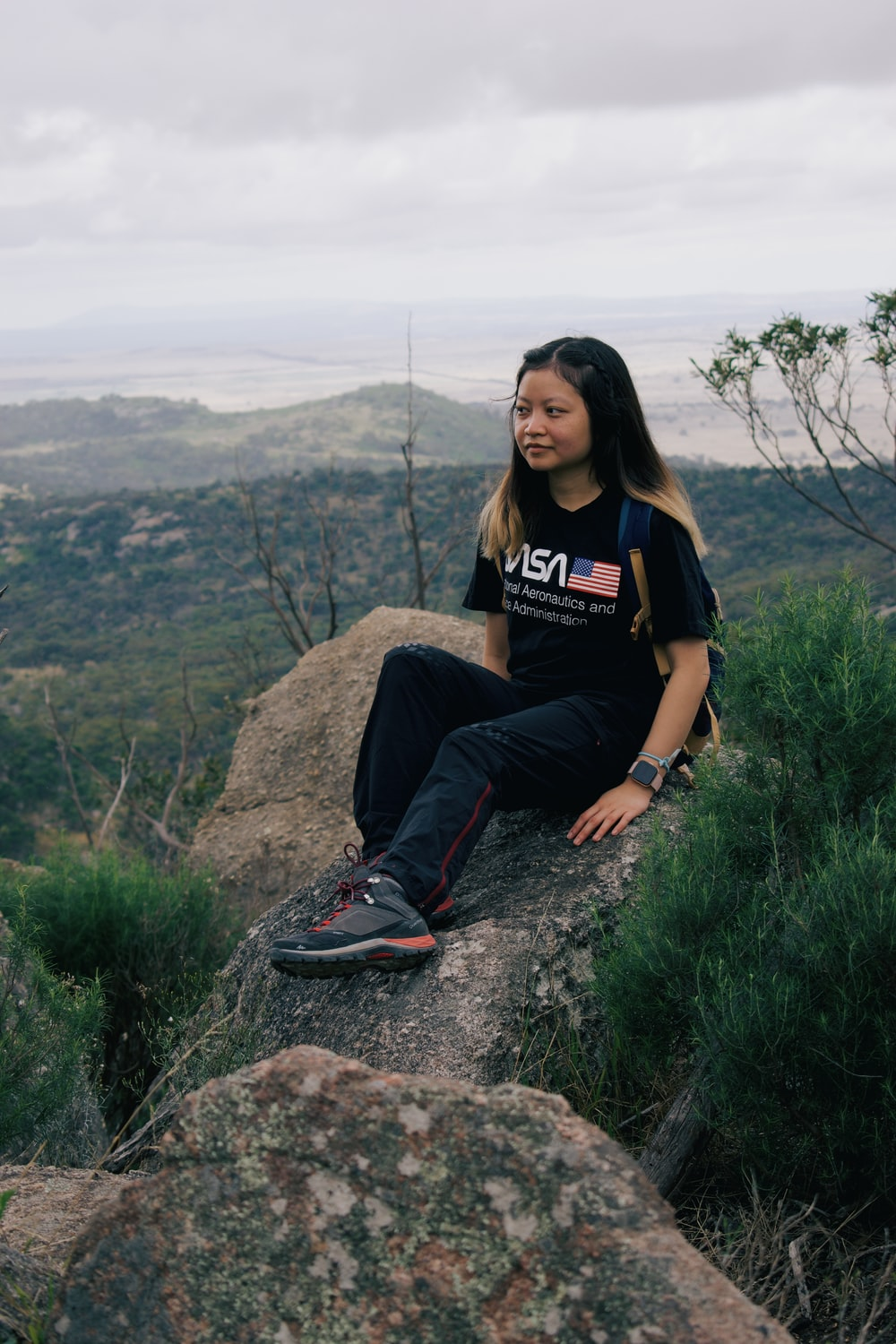 woman in black crew neck t-shirt sitting on rock during daytime
