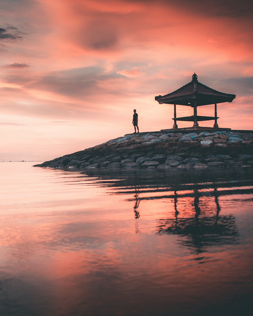 person standing on rock formation near body of water during sunset