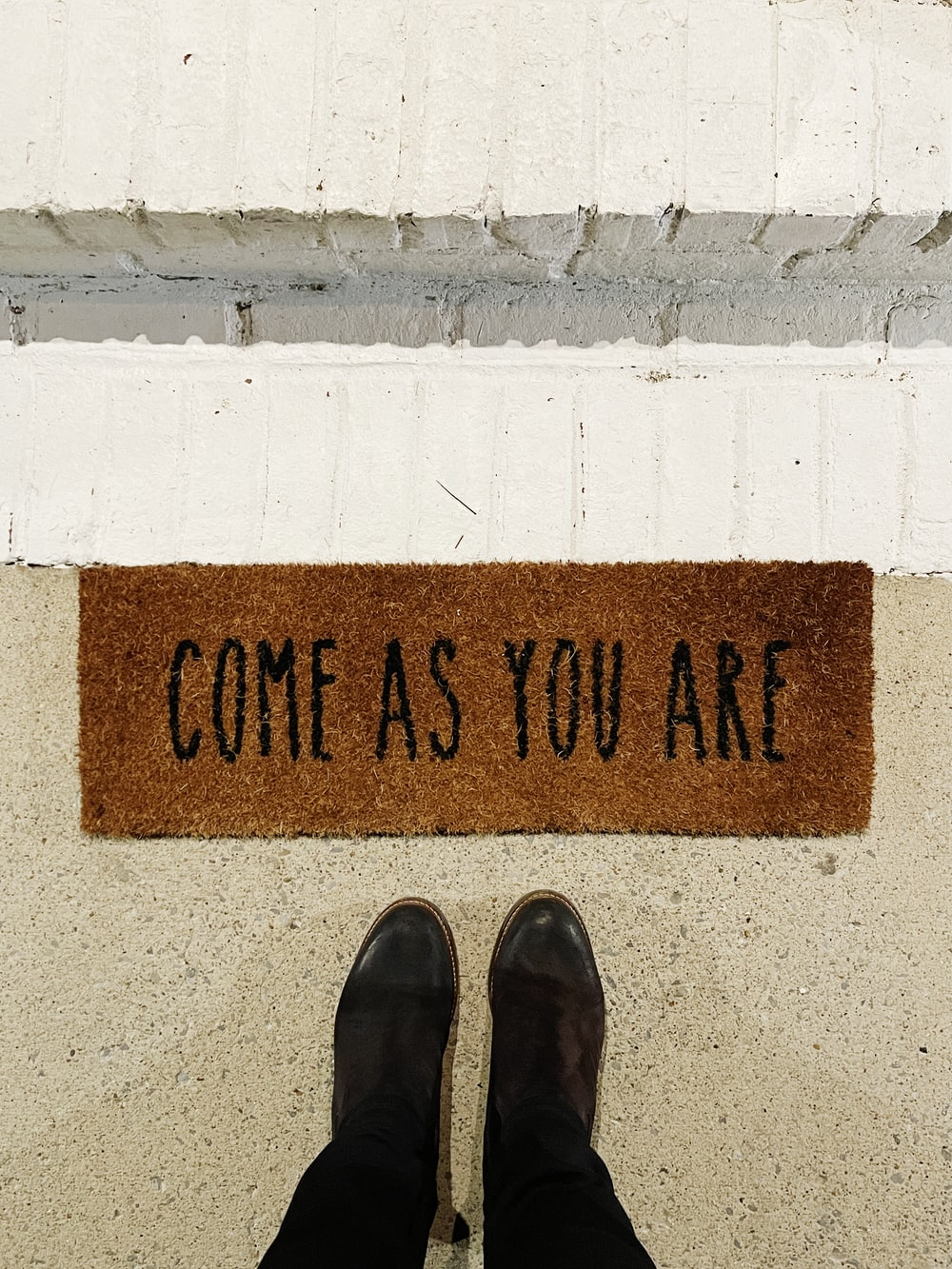 person standing on brown and black welcome printed floor mat