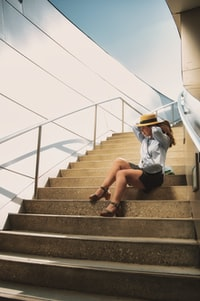 woman in white shirt and black shorts sitting on gray concrete staircase
