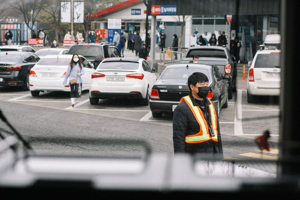 man in yellow jacket walking on pedestrian lane during daytime