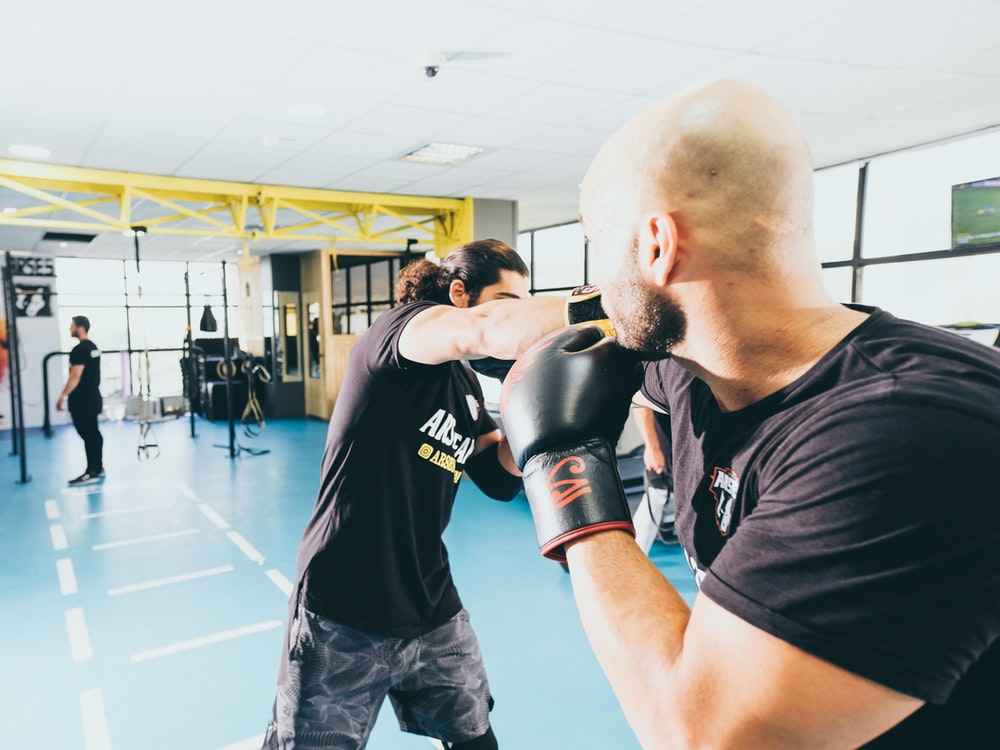 man in black crew neck t-shirt and black shorts wearing black boxing gloves