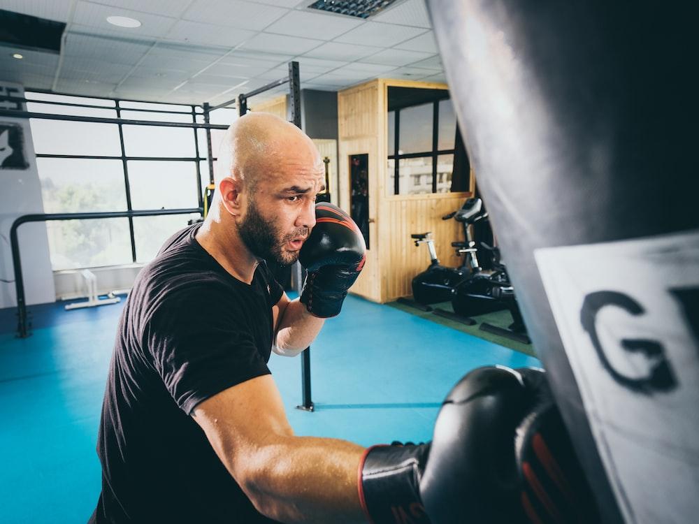 man in black t-shirt wearing black boxing gloves