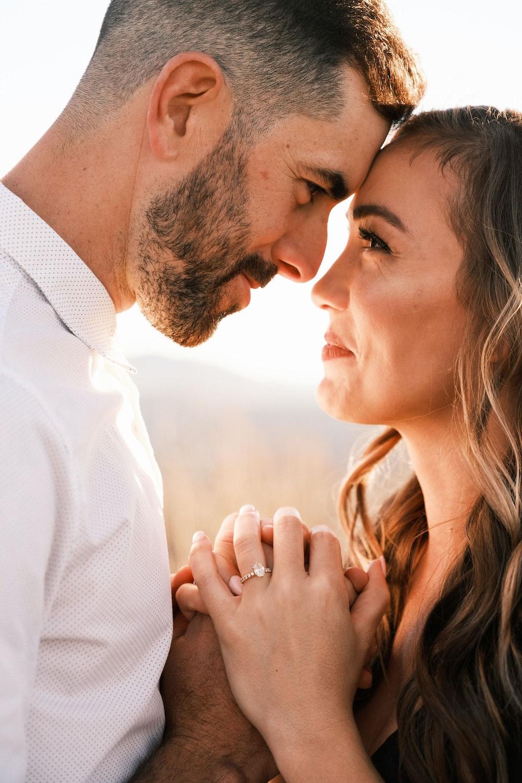 man in white dress shirt kissing woman in brown shirt