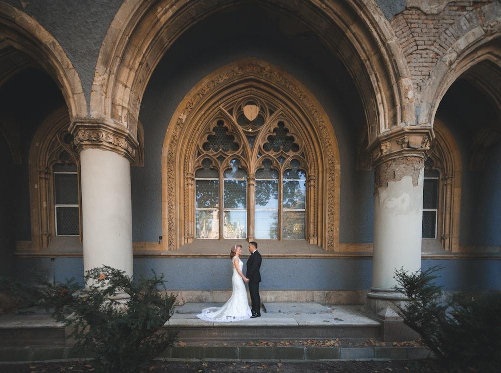 woman in white wedding dress standing in front of brown wooden door