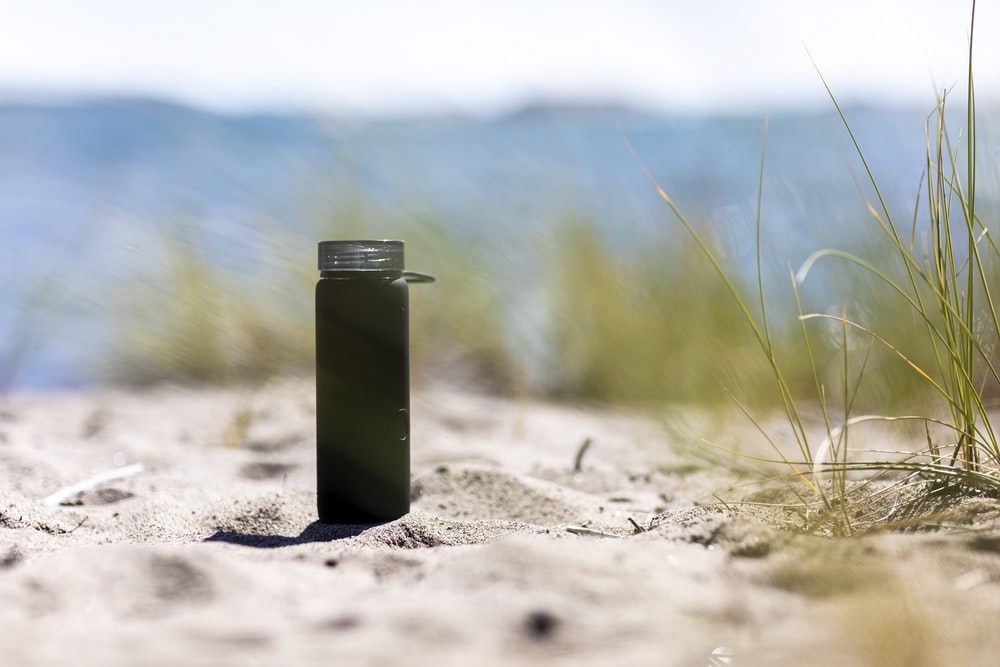 green and silver steel container on brown sand during daytime