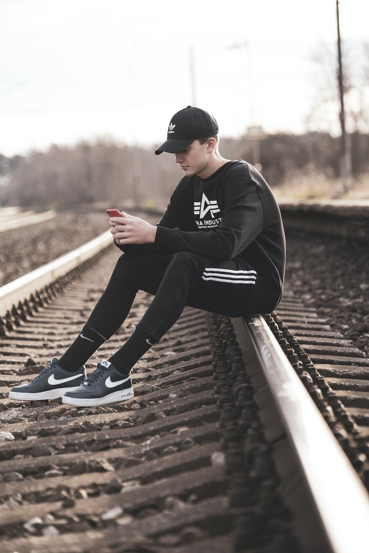man in black hoodie and black pants sitting on train rail during daytime
