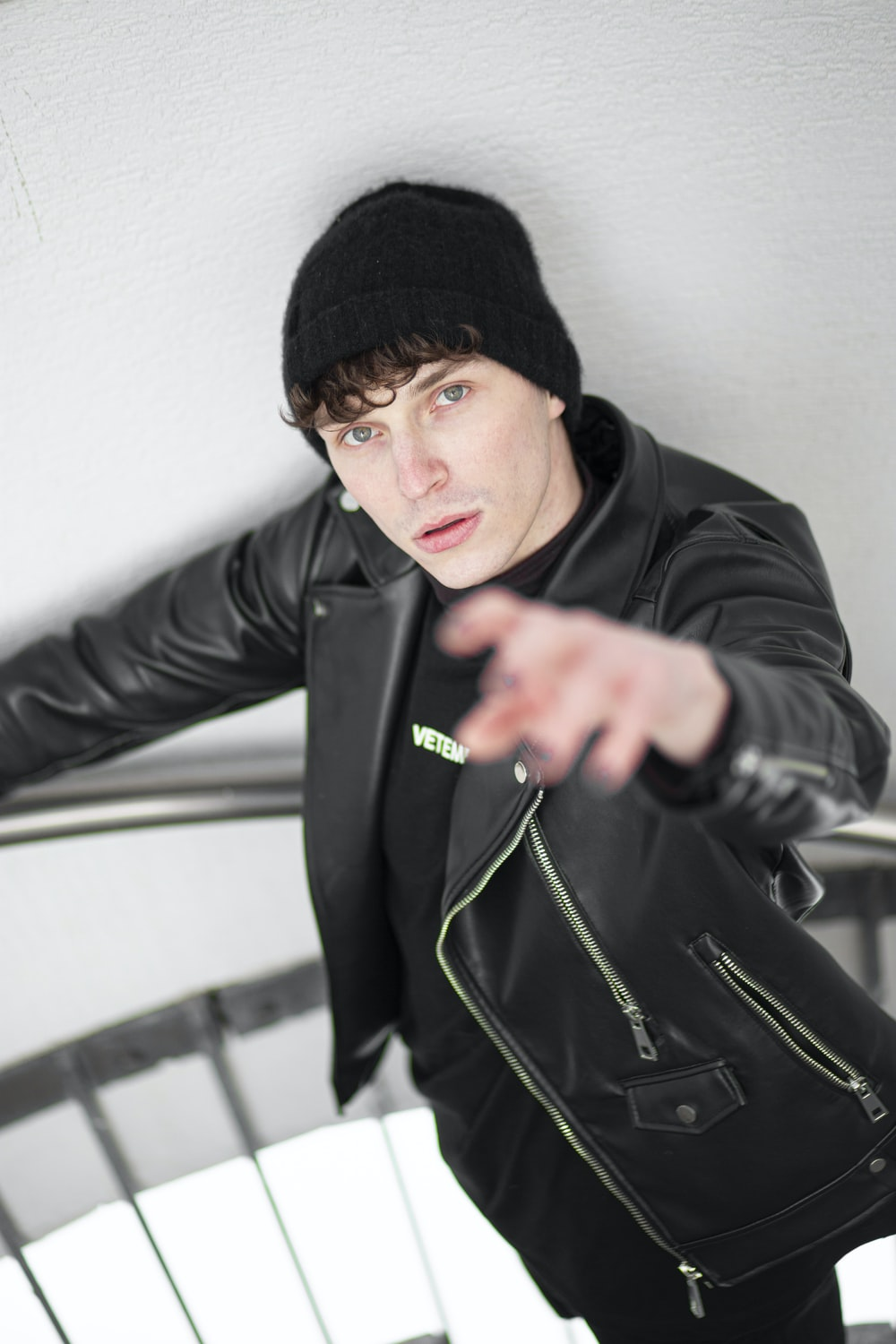 man in black knit cap and black leather jacket