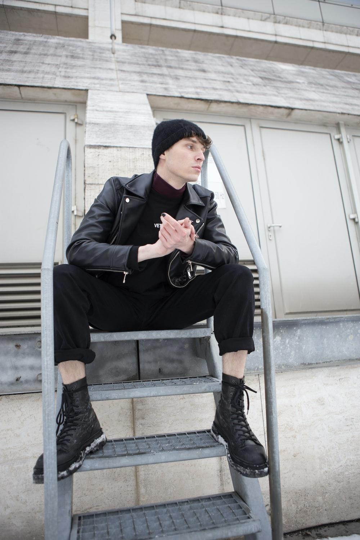 man in black suit jacket and black pants sitting on black chair
