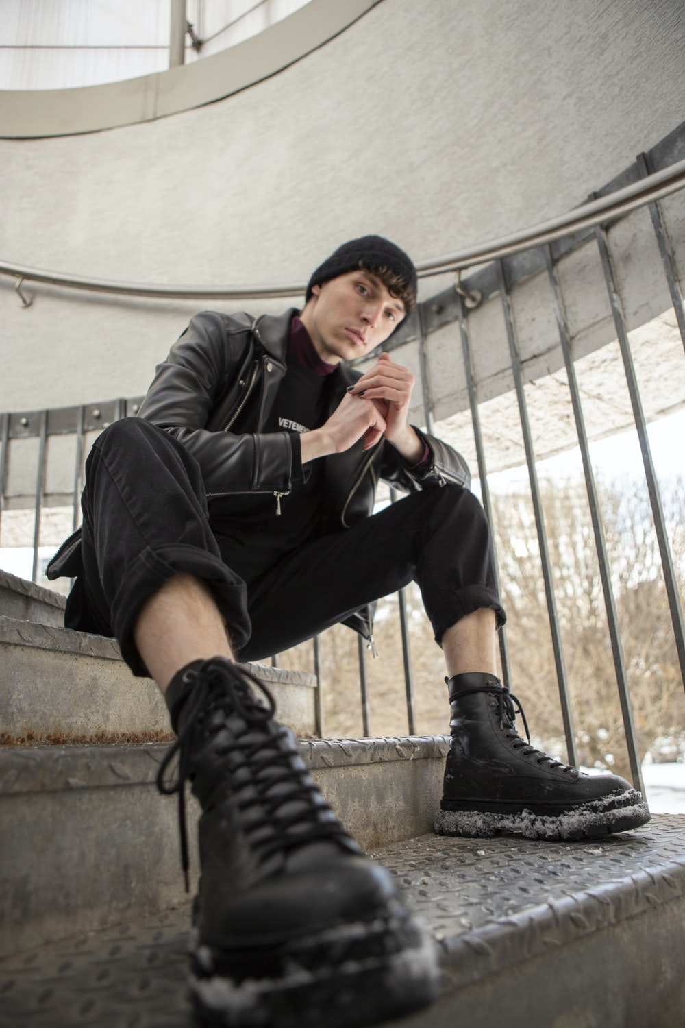 man in black leather jacket and blue denim jeans sitting on concrete stairs