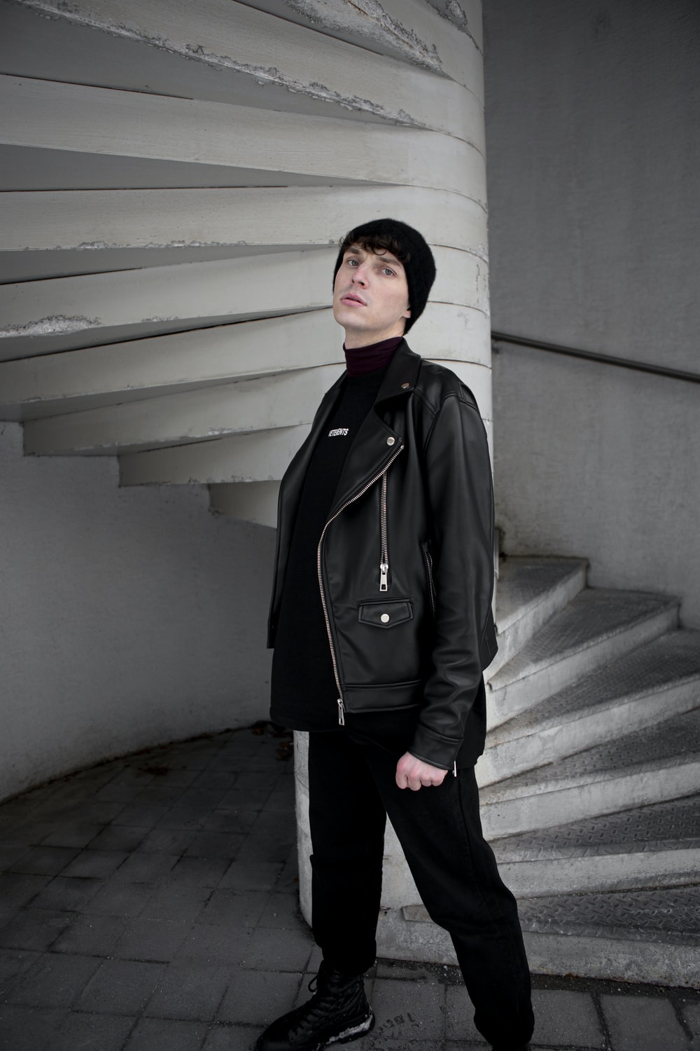 woman in black coat standing on gray concrete stairs