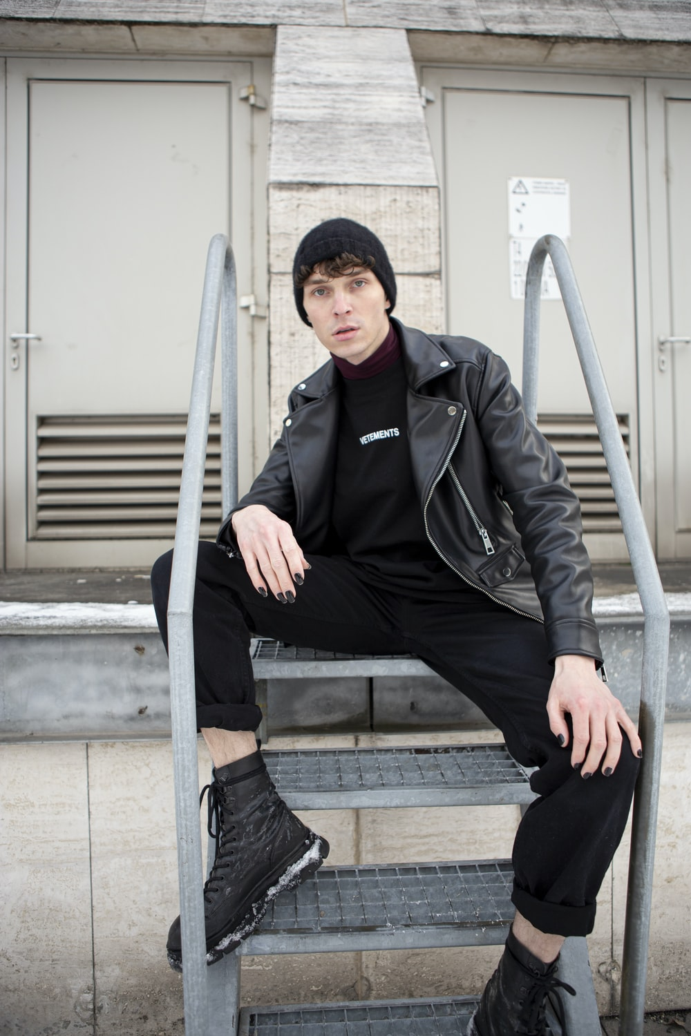 man in black jacket and black pants sitting on stairs