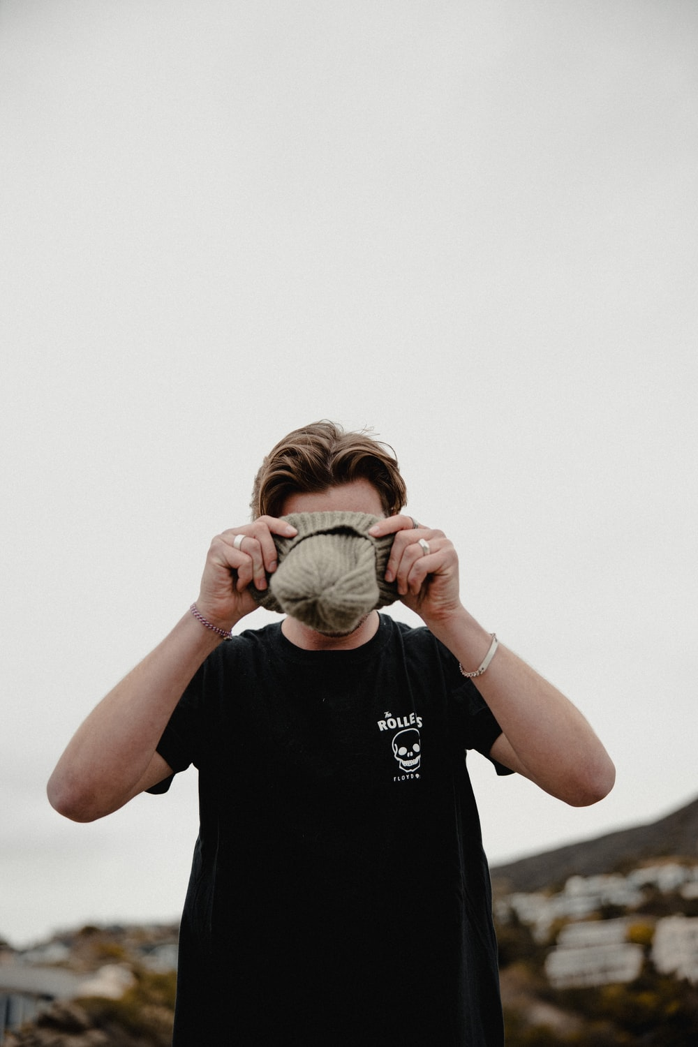 man in black crew neck t-shirt covering his face with green and white textile