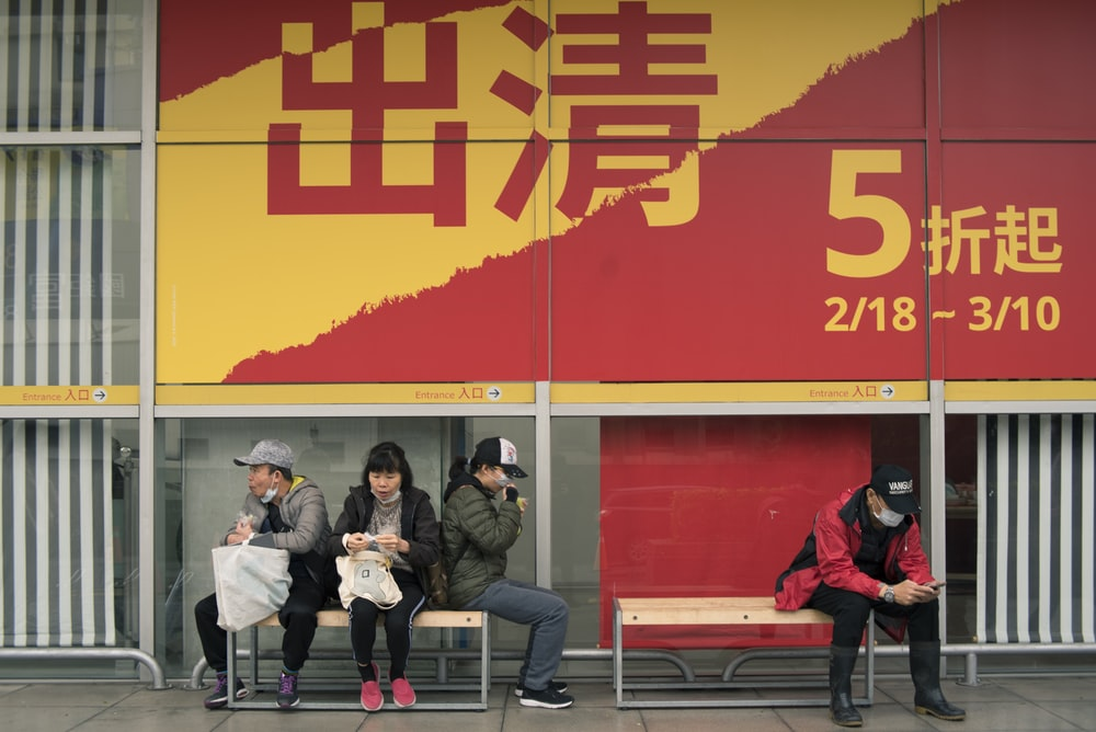 people sitting on bench near red wall