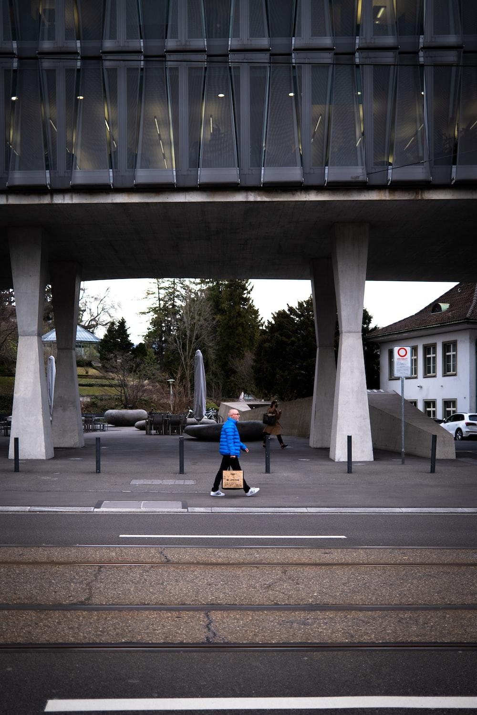 man in blue jacket and black pants walking on sidewalk during daytime