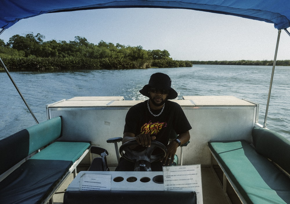 man in black and yellow crew neck t-shirt sitting on boat during daytime