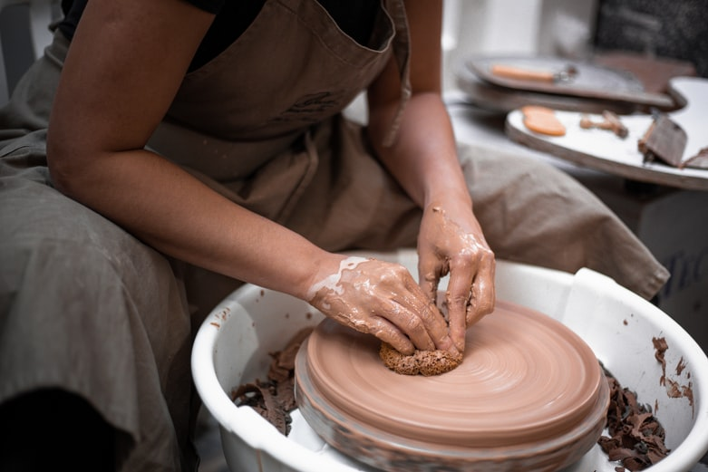 person making clay pot with brown clay