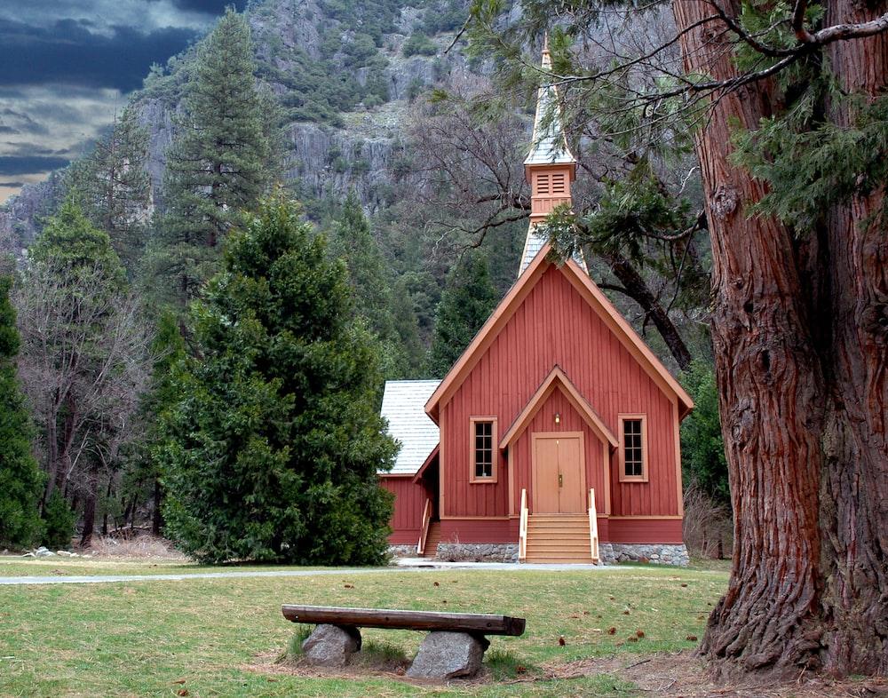 brown wooden bench near brown wooden church