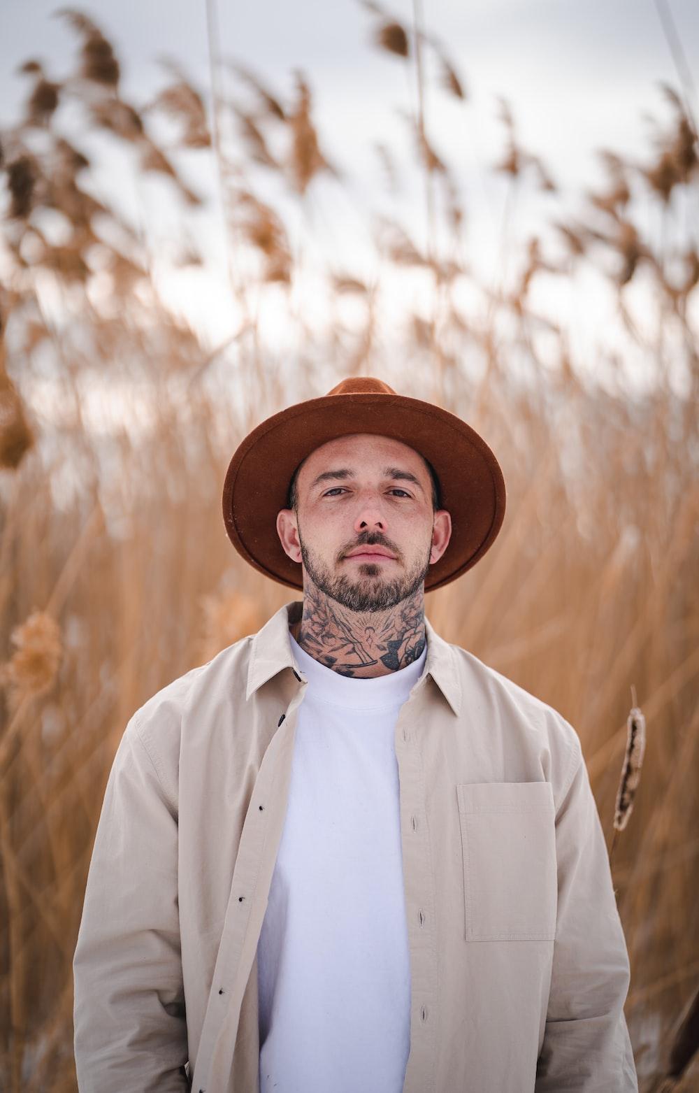 man in white button up shirt wearing brown hat