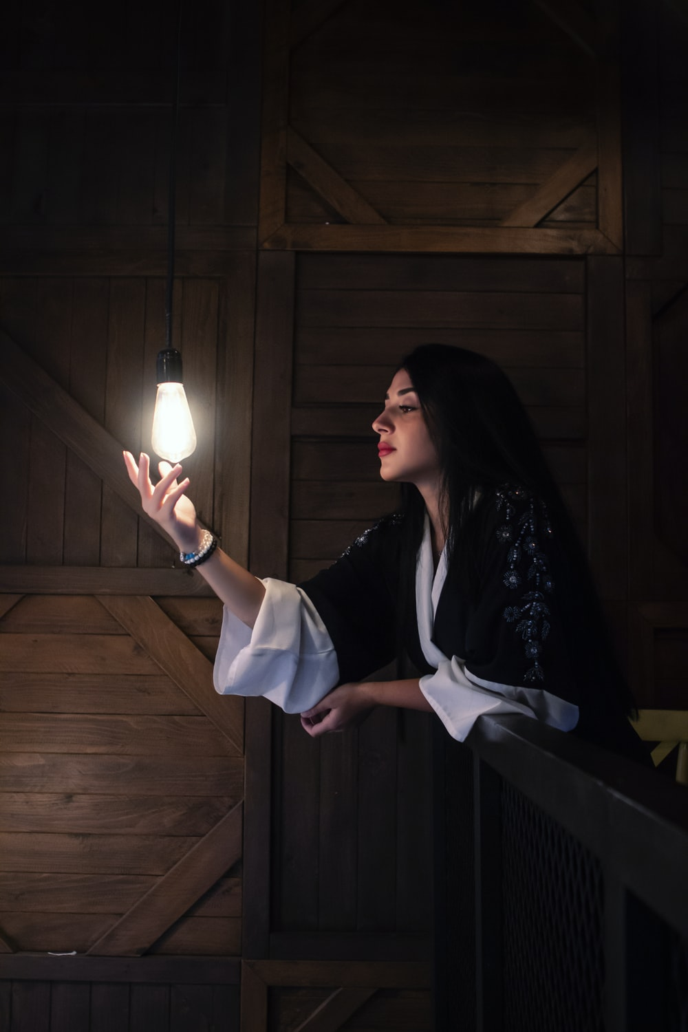 woman in black and white dress holding white light bulb