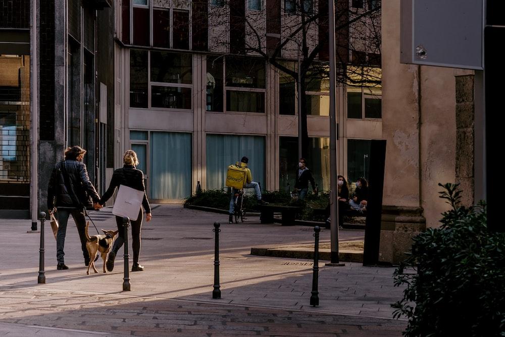 2 women sitting on bench near building during daytime