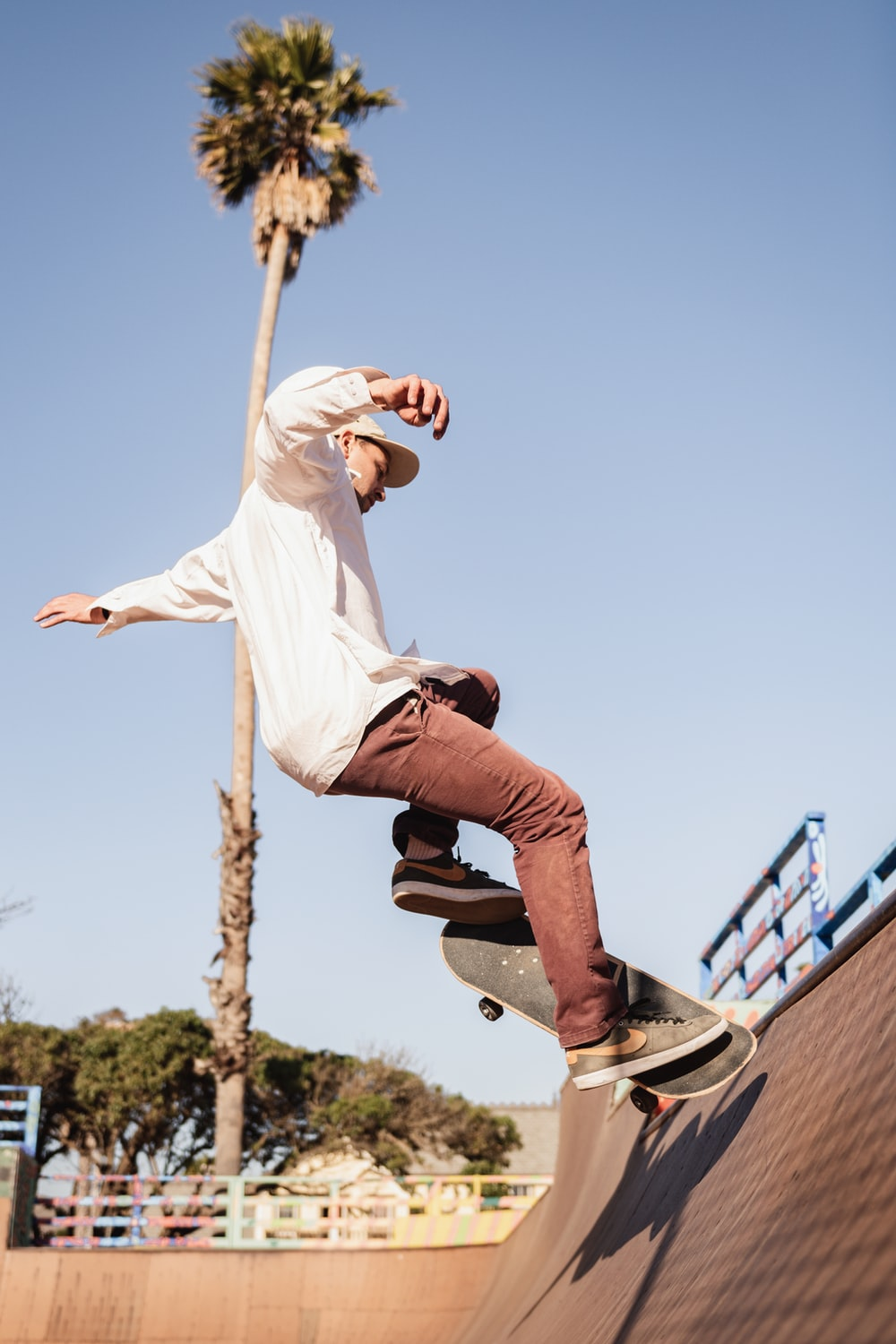 man in white t-shirt and blue denim jeans jumping on blue metal railings during daytime