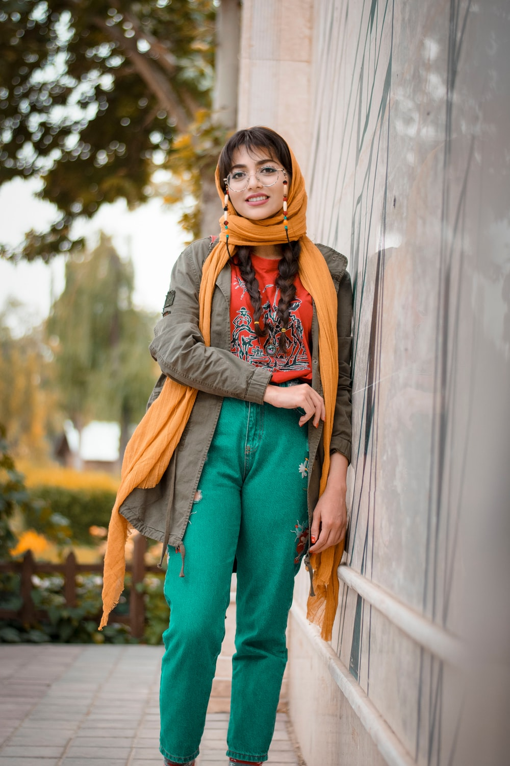 woman in gray scarf and brown coat standing beside gray wall