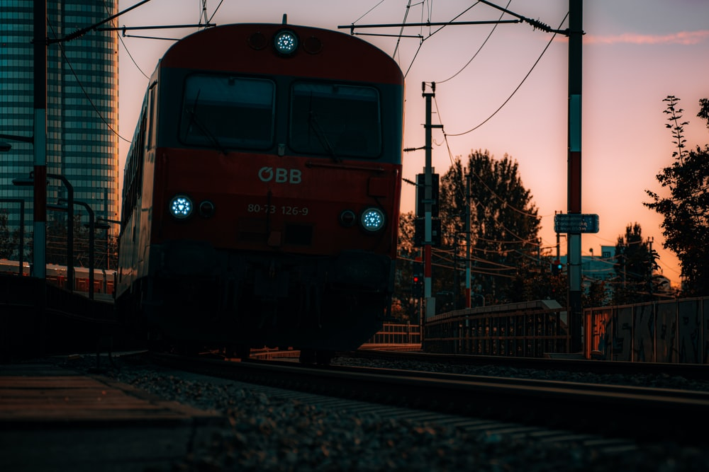 blue and red train on rail road during daytime