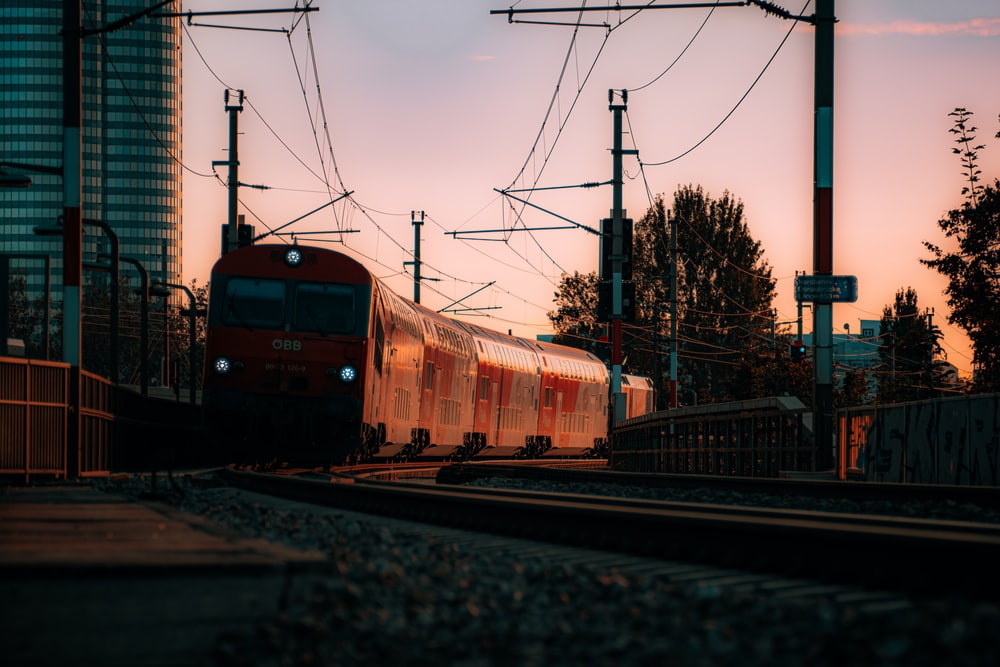 red and yellow train on rail tracks during daytime