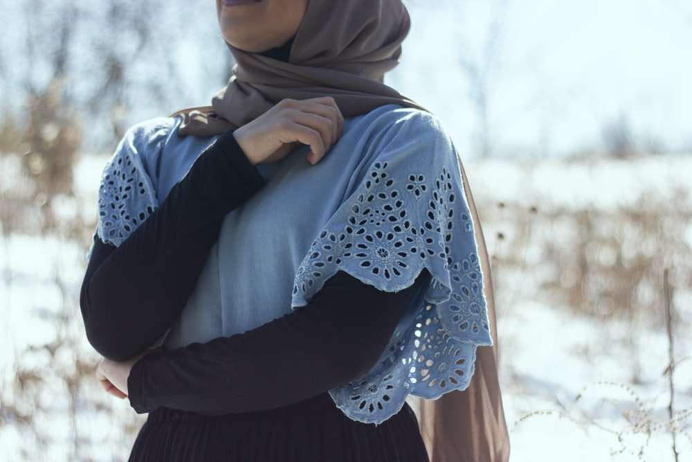 woman in blue hijab and white long sleeve shirt