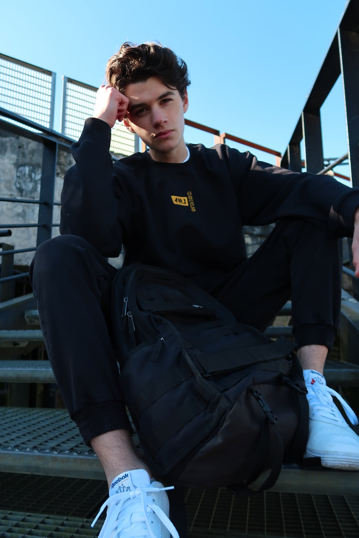 man in black jacket sitting on black chair