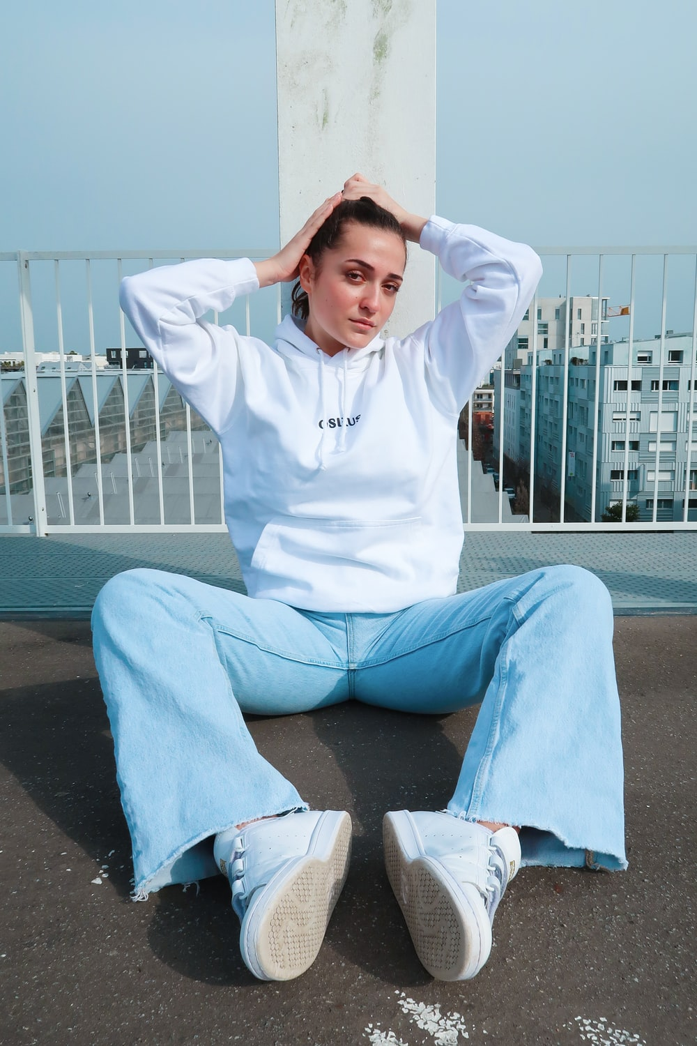 man in white hoodie and blue pants sitting on concrete bench