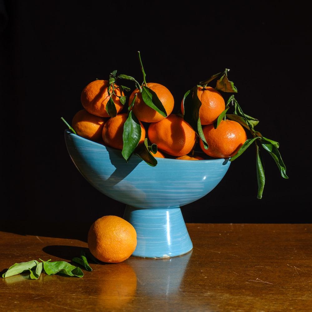 orange fruits in blue glass bowl