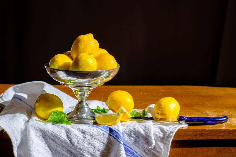 yellow lemon fruit on clear glass bowl