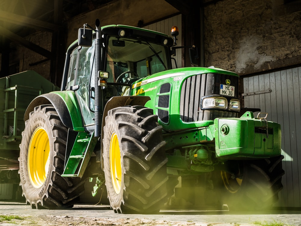 green and yellow tractor in garage