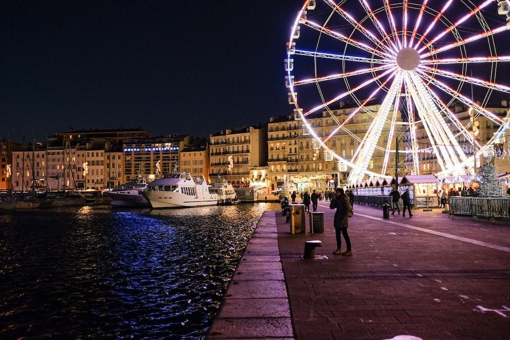 people walking on sidewalk near ferris wheel during night time