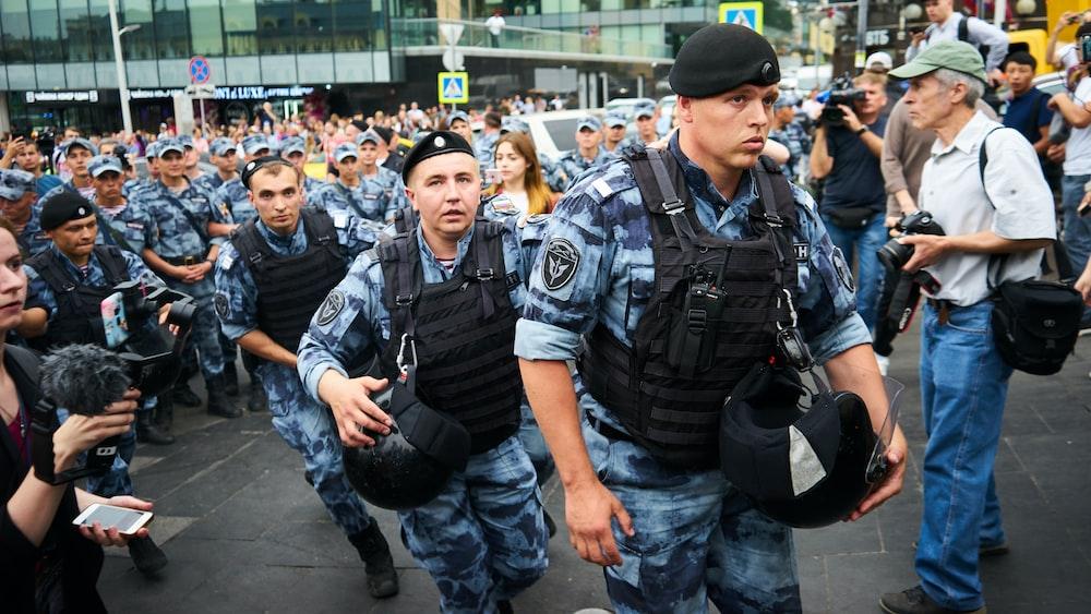 men in black police uniform standing on street during daytime