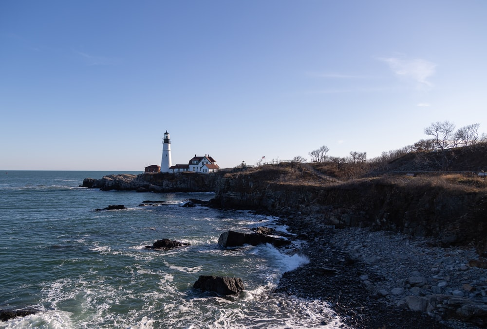 white lighthouse on brown rock formation near body of water during daytime