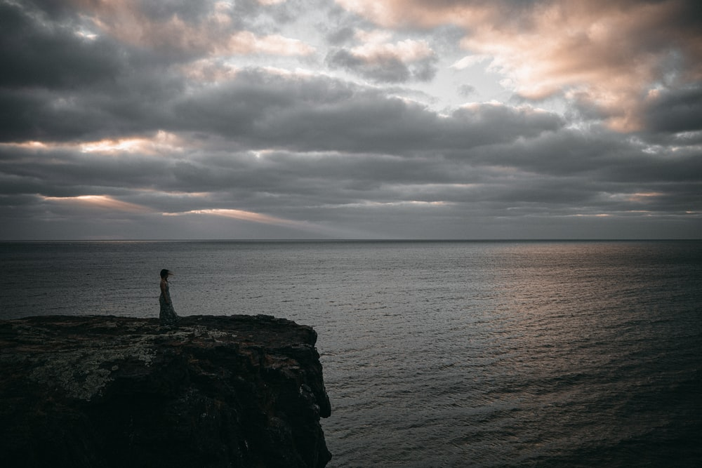 silhouette of person standing on rock formation near sea during daytime