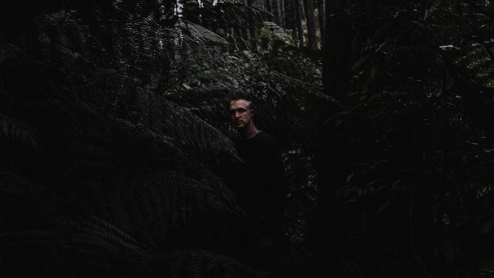 man in black long sleeve shirt standing beside green plant